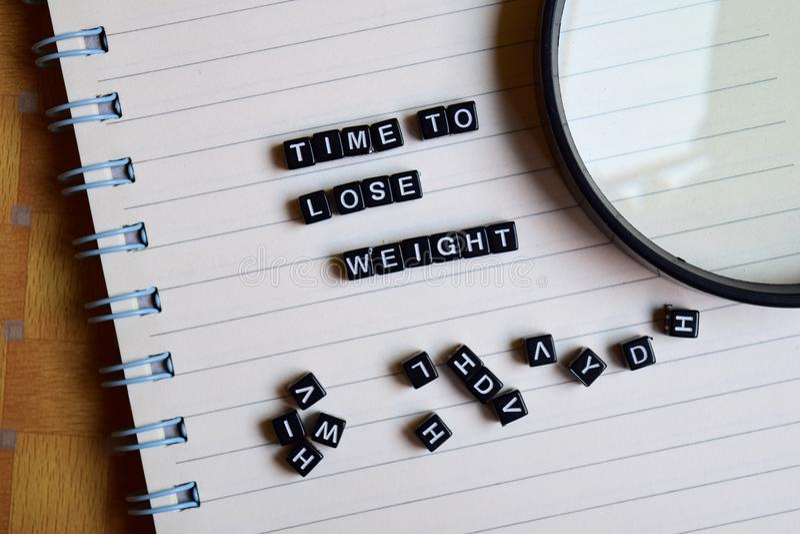 Begrepp av Tid som förlorar vikt på träkuber med böcker i bakgrund arkivfoto