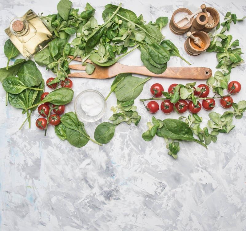 Begrepp av vegetarisk mat för matlagning, körsbärsröda tomater, olika salladvariationer, spenatsmaktillsatser, kryddor, oliv, sal royaltyfria foton