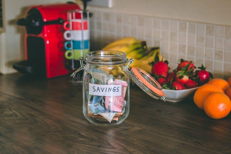 Begrepp: besparingar skorrar med pengar inom av den överst av tabellen för kök` s fotografering för bildbyråer
