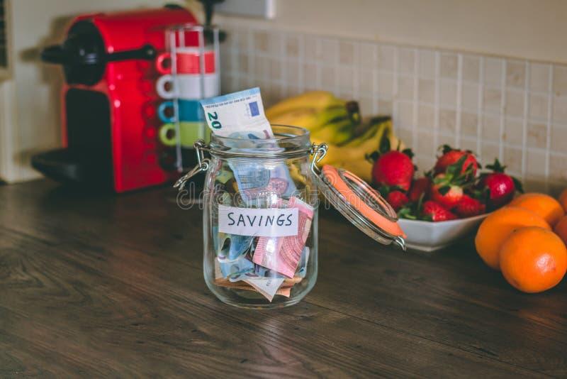 Begrepp: besparingar skorrar med pengar inom av den överst av tabellen för kök` s arkivfoto