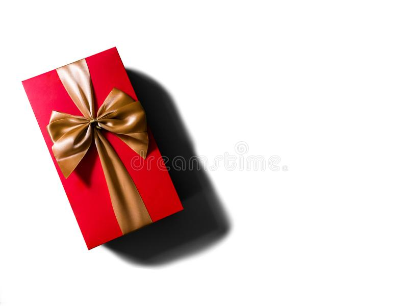 Begrepp eller idé av den plana sikten av den röda gåvaasken med det guld- bandet eller pilbågen arkivfoto