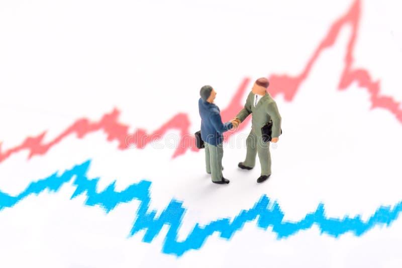 Begrepp för affärsinvestering och finans Miniatyrfolkstatyettaffärsmän står på finansgraf royaltyfria foton