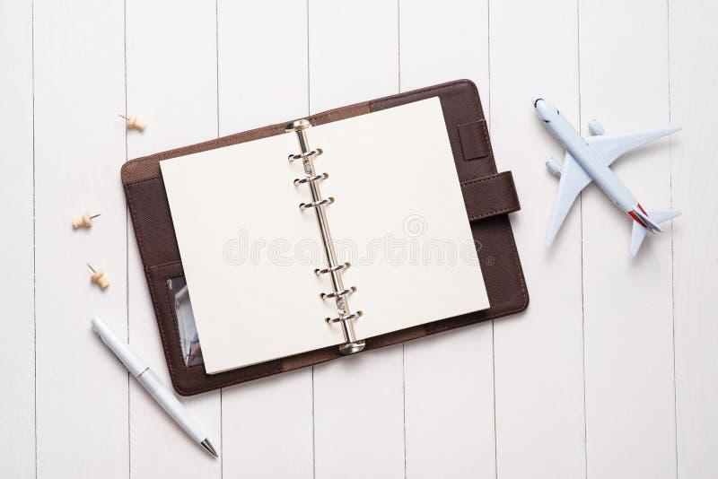 Begrepp för affärstur Flygplan och öppen anteckningsbok för mellanrum för ditt arkivbild