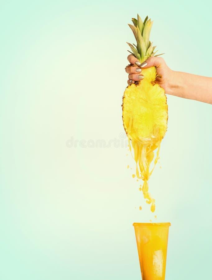 Begrepp för ananasfruktsaft Hållande halva för kvinnlig hand av ananas och pressfruktsaft in i exponeringsglas royaltyfri foto