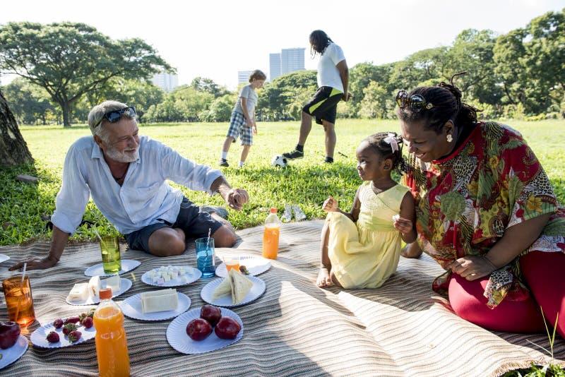 Begrepp för avkoppling för samhörighetskänsla för familjpicknick utomhus royaltyfria foton