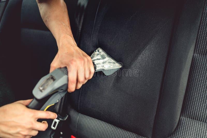Begrepp för bilomsorg, yrkesmässig ånga som dammsuger stoppningen av baksäten arkivbild