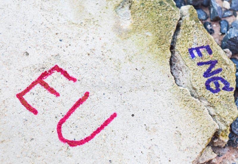 Begrepp för Brexit UK EU-folkomröstning med ordet FN och engelska på stenväggen royaltyfria foton