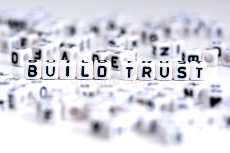Begrepp för byggandeförtroendeprocess med belade med tegel bokstäver på vit bakgrund arkivfoto