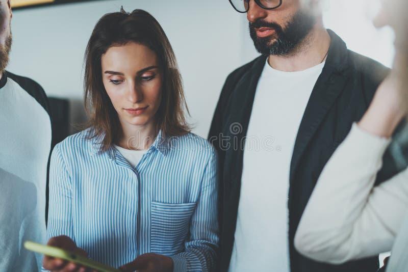 Begrepp för Coworkersaffärsmöte Unga kvinnor som rymmer den mobila smartphonehanden och diskussionsnyheterna med hennes kollegor fotografering för bildbyråer