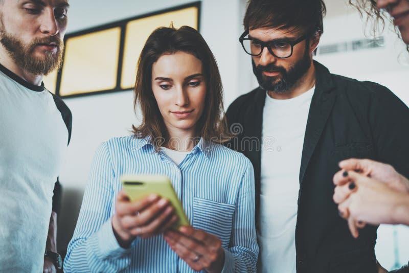Begrepp för Coworkersaffärsmöte Unga kvinnor som rymmer den mobila smartphonehanden och visar information till hennes kollegor arkivfoton