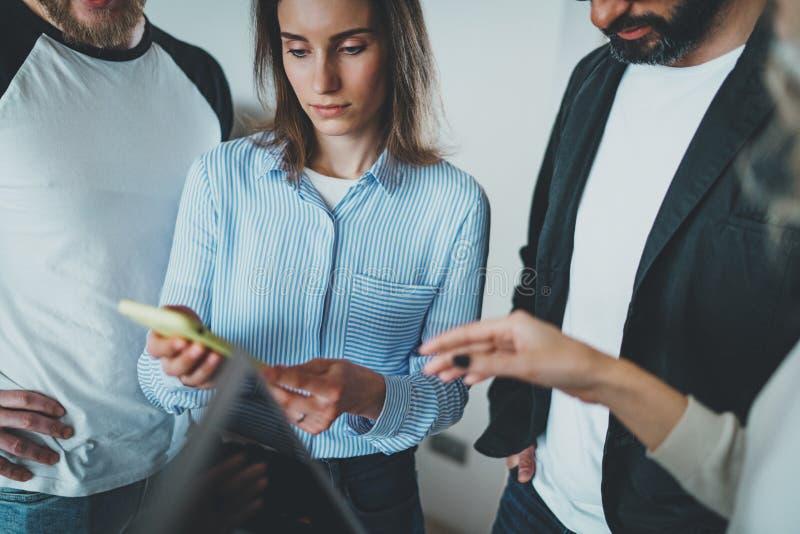 Begrepp för Coworkersaffärsmöte Unga kvinnor som rymmer mobiltelefonhanden och diskussionsnyheterna med hennes kollegor arkivfoto
