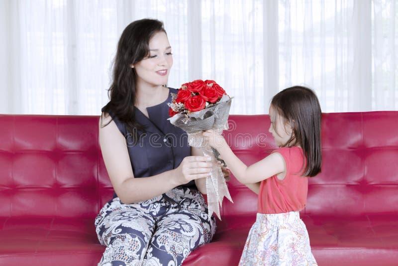 Begrepp för dag för moder` s: Dottern ger en bukett av röda rosor till modern arkivfoton