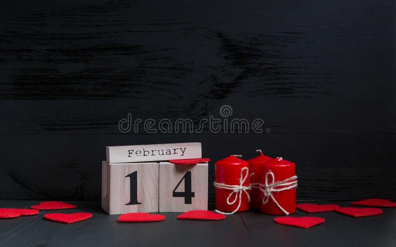 Begrepp för dag för St-valentin` s kalendern med nummer och månad lägger på den svarta träbakgrunden med röda stearinljus arkivfoton