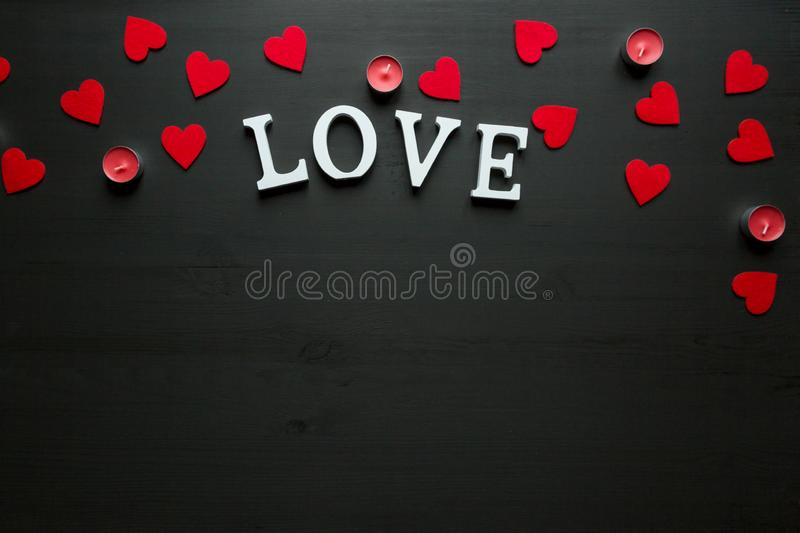 Begrepp för dag för St-valentin` s ordet FÖRÄLSKELSE lägger på den trätillbaka jordningen med röda stearinljus och hjärtor arkivbild