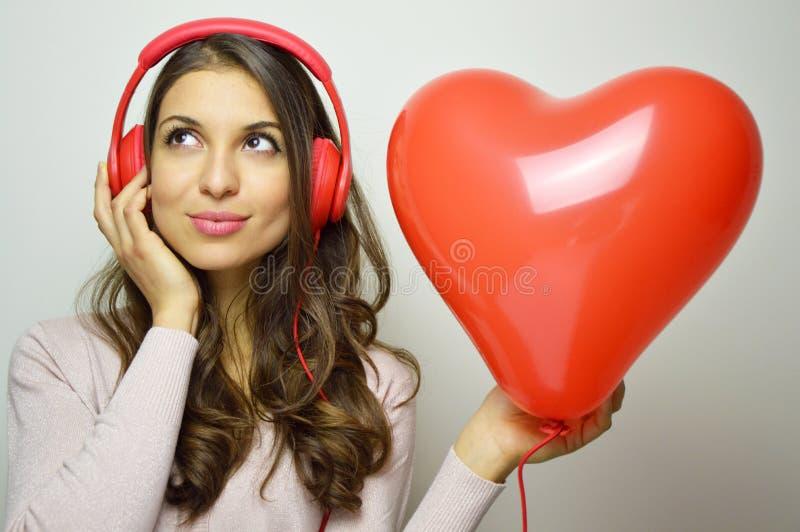 Begrepp för dag för valentin` s Älskvärd flicka med röd hörlurar som lyssnar till stämman av hans hjärta Gullig ung kvinna som ly arkivbild