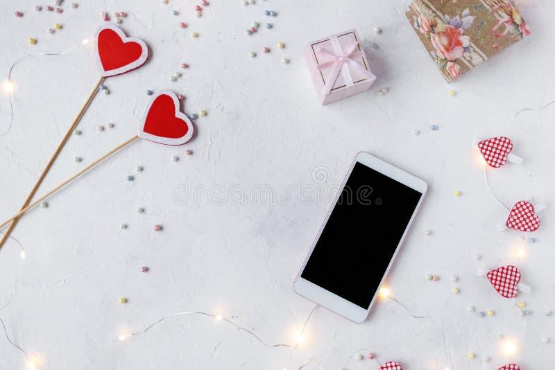 Begrepp för dag för valentin` s Hjärtor konfettier, smartphone, dekor, ljus på en ljus bakgrund royaltyfri fotografi