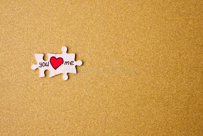 Begrepp för dag för valentin` s par av pussel med hjärtor på en guld- bakgrund kopiera avstånd Selektivt fokusera royaltyfria foton