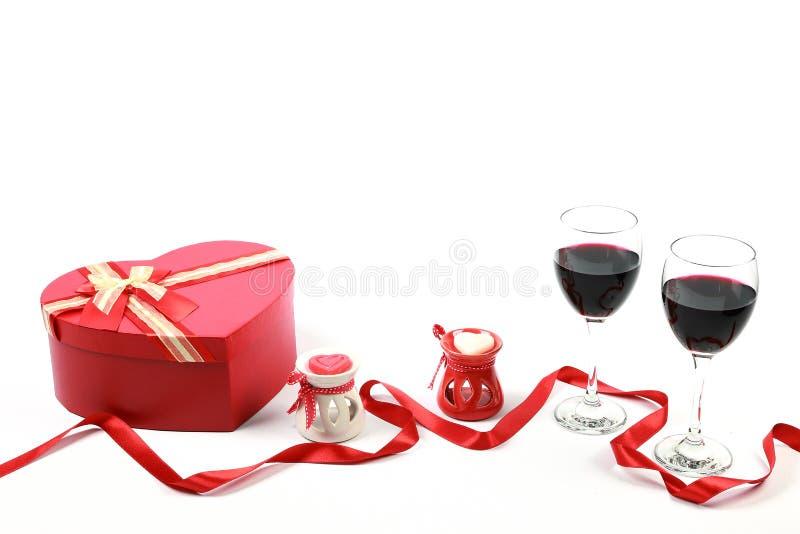 Begrepp för dag för valentin` s Två exponeringsglas av rött vin med hjärta formade stearinljus- och gåvaasken med det röda bandet royaltyfria bilder