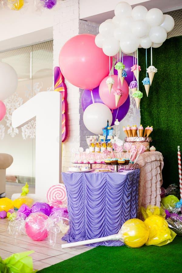 Begrepp för födelsedagparti, godisstång för barn Enormt nummer ett, tabell med sötsaker och efterrätter, moln från ballonger och  arkivbild