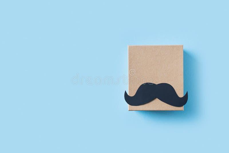 Begrepp f?r faderdag med den g?vaasken och mustaschen p? bl? bakgrund arkivbilder