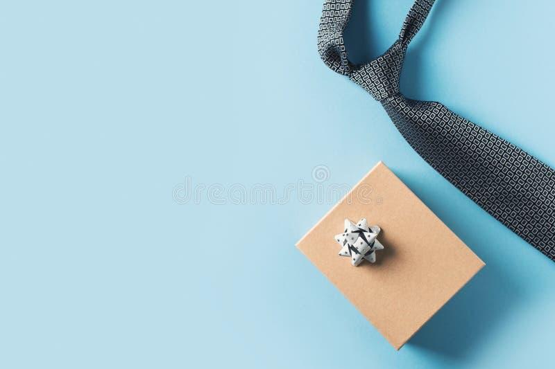 Begrepp för faderdag med det gåvaasken och bandet på blå bakgrund arkivfoto