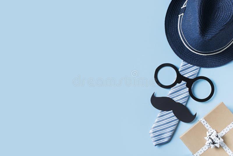 Begrepp f?r faderdag med hatten, exponeringsglas och bandet p? bl? bakgrund arkivfoton