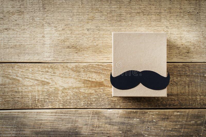 Begrepp f?r faderdag med mustasch- och g?vaasken p? tr?bakgrund royaltyfri bild