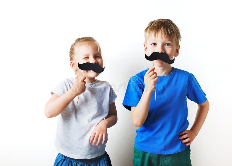 Begrepp f?r faderdag, tv? lilla caucasian ungar med mustaschen p? vit bakgrund royaltyfria foton