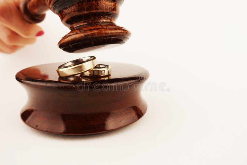 Begrepp för familjlag eller skilsmässadekret med vigselringar under domareauktionsklubban arkivbild
