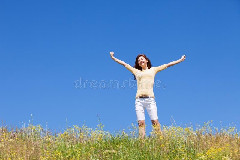Begrepp för folkfrihetsframgång drömmar flyger lyckligt till windskvinnan Landskap av gräs- och blommasommarfältet på solig dag royaltyfri bild