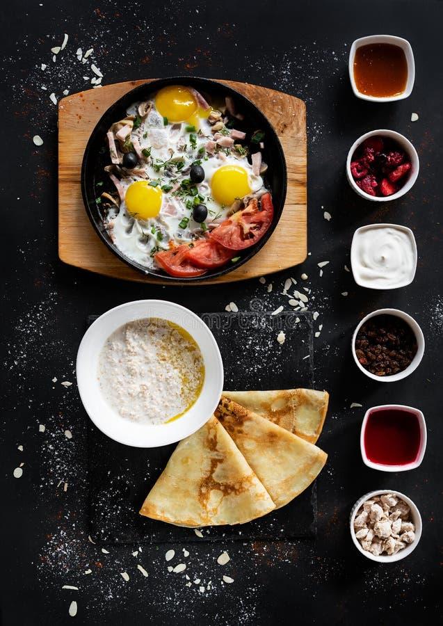 Begrepp för frukostmat Mörk bakgrund med pannan med ägg med grönsaker, havremjölet med pannkakor och sex sorter av såser Sunt royaltyfria bilder