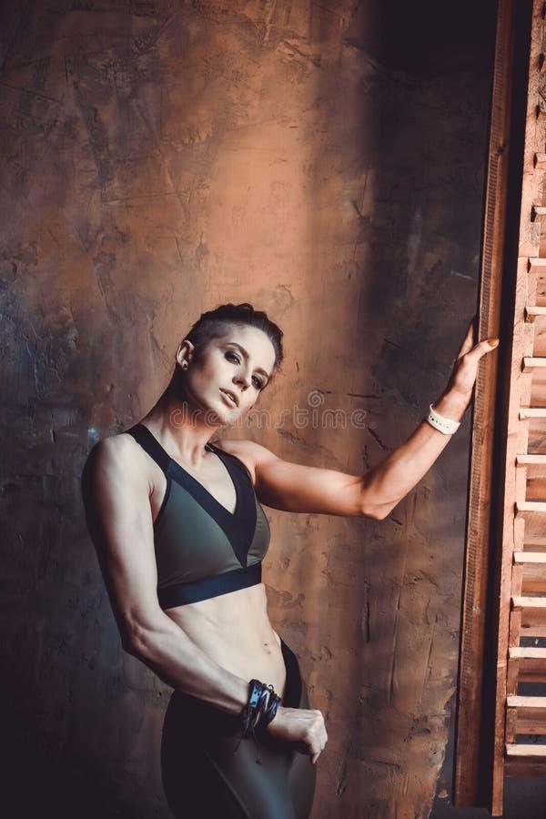 Begrepp för genomkörare för konditionstyrkautbildning - sexig sportflicka för muskulös kroppsbyggare som gör övningar i idrottsha royaltyfria foton