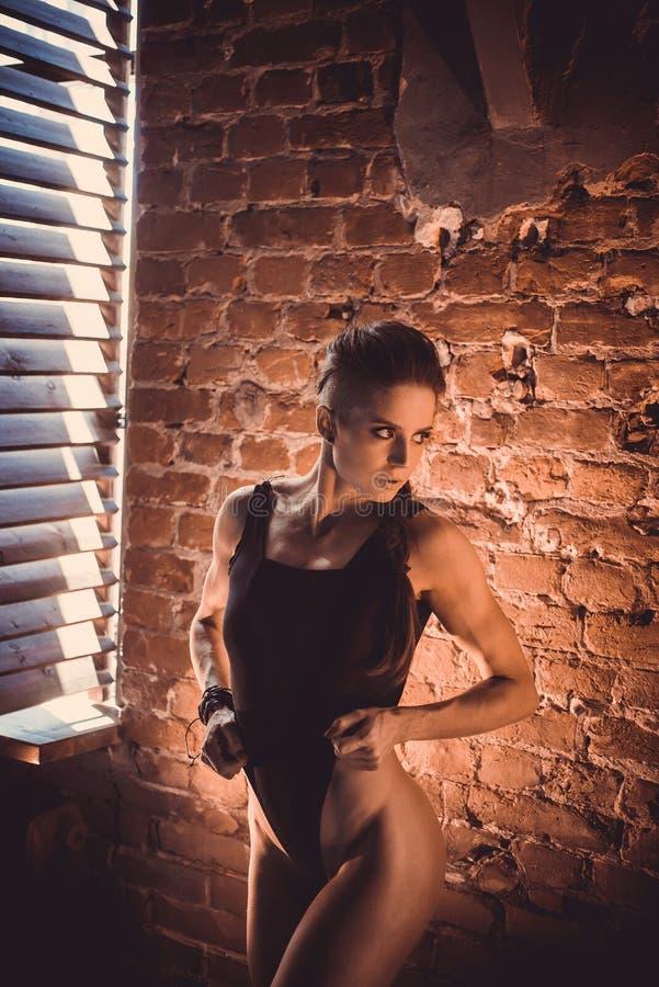 Begrepp för genomkörare för konditionstyrkautbildning - sexig sportflicka för muskulös kroppsbyggare som gör övningar i idrottsha royaltyfri fotografi