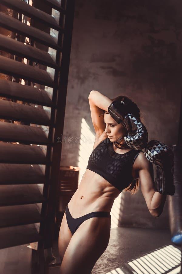 Begrepp för genomkörare för konditionstyrkautbildning - sexig sportflicka för muskulös kroppsbyggare som gör övningar i idrottsha arkivfoto