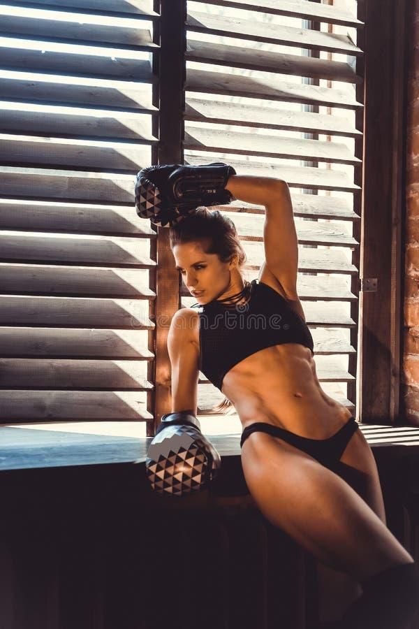 Begrepp för genomkörare för konditionstyrkautbildning - sexig sportflicka för muskulös kroppsbyggare som gör övningar i idrottsha royaltyfri foto
