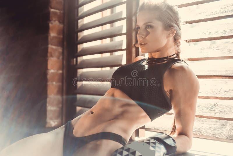 Begrepp för genomkörare för konditionstyrkautbildning - sexig sportflicka för muskulös kroppsbyggare som gör övningar i idrottsha fotografering för bildbyråer