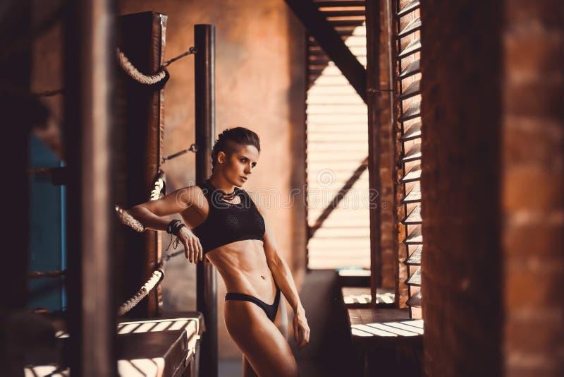 Begrepp för genomkörare för konditionstyrkautbildning - sexig sportflicka för muskulös kroppsbyggare som gör övningar i idrottsha arkivfoton