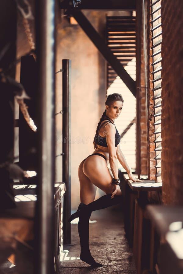 Begrepp för genomkörare för konditionstyrkautbildning - sexig sportflicka för muskulös kroppsbyggare som gör övningar i idrottsha arkivbild