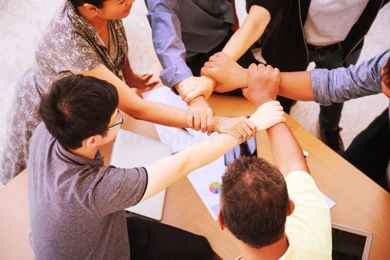 Begrepp för händer för möte för teamwork för affärsfolk sammanfogande i regeringsställning, genom att använda idéer, diagram, dat arkivfoton