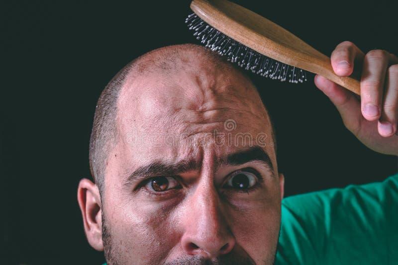 Begrepp för hårförlust Skallig man som använder hårborsten på icke existerande hår royaltyfria foton