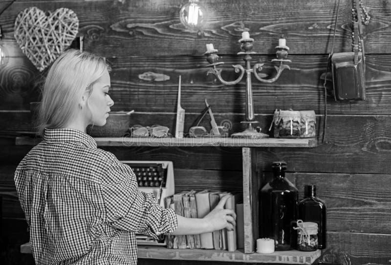Begrepp för hem- arkiv Flicka som söker efter boken i hus av skogsvaktaren Flicka i tillfällig dräkt i trätappninginre royaltyfria bilder