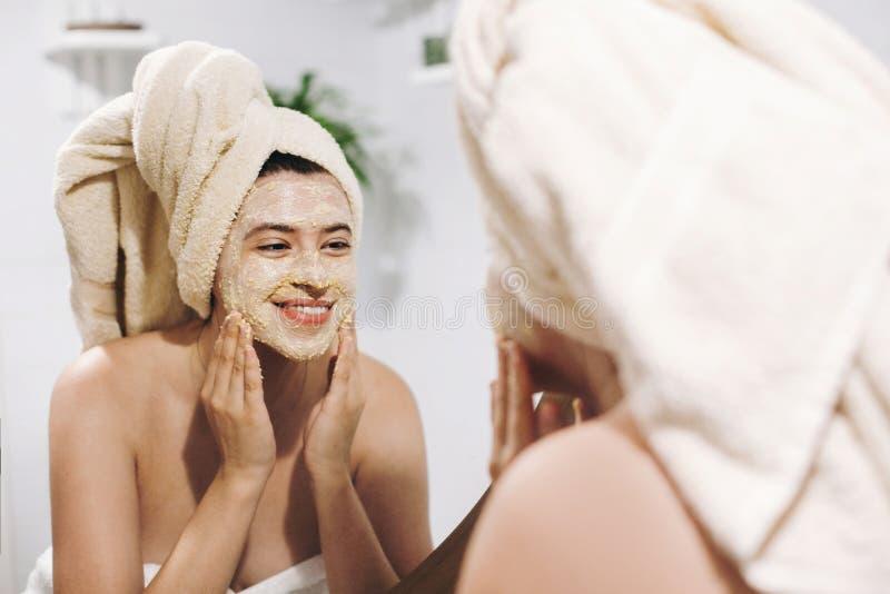 Begrepp för hudomsorg Den unga lyckliga kvinnan i handduken som gör ansikts- massage med den organiska framsidan, skurar och ser  royaltyfria bilder