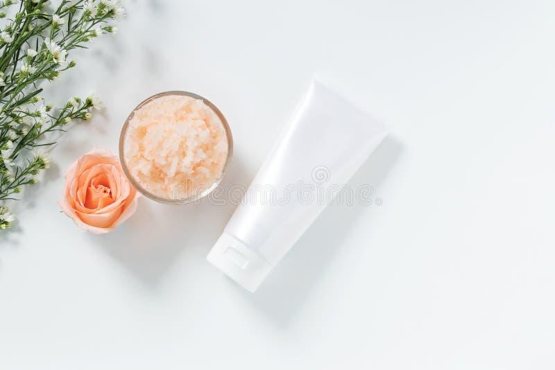 Begrepp för hudomsorg plant lägger av skincareboter utformar i den vita åtstramningrörpacken med den tomma etiketten och saltar b arkivfoto