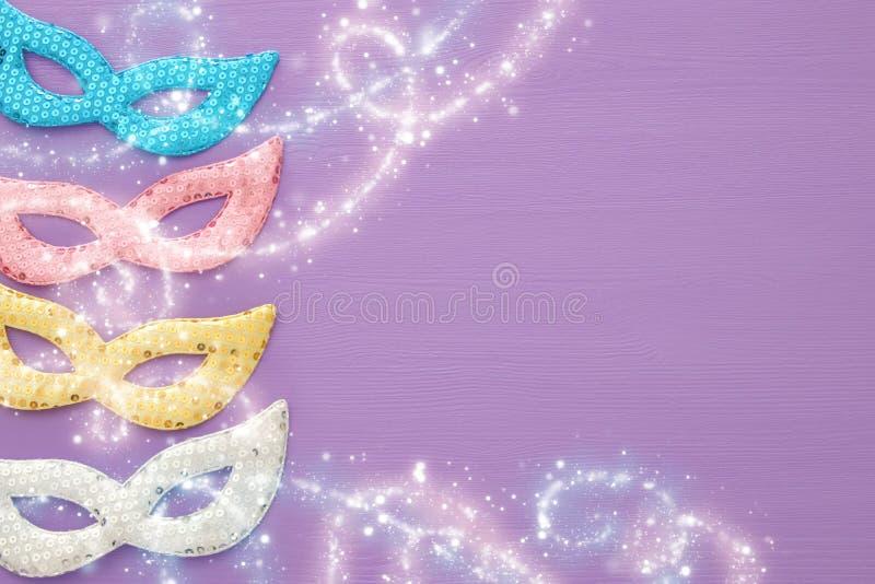 begrepp för karnevalpartiberöm med färgrik pastellfärgat rosa, guld-, silver och blåa maskeringar över purpurfärgad träbakgrund T vektor illustrationer