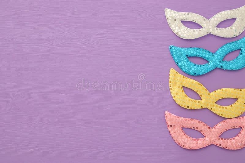 begrepp för karnevalpartiberöm med färgrik pastellfärgat rosa, guld-, silver och blåa maskeringar över purpurfärgad träbakgrund T royaltyfria bilder