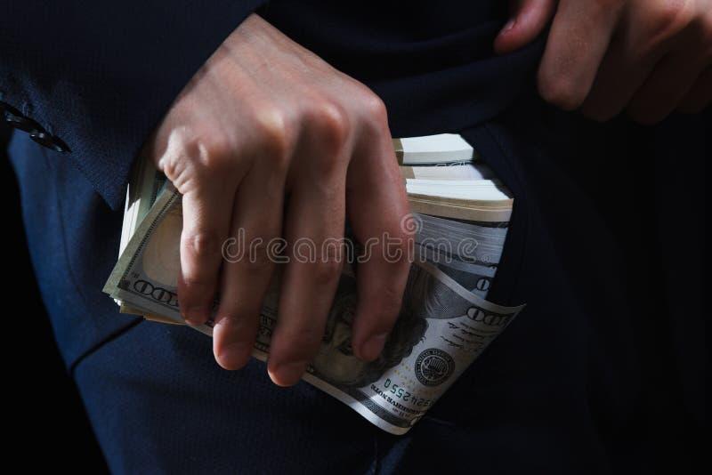 Begrepp för korruption, konkurs, ok, brott som muter, bedrägeri Packe av handen för dollarkassa in arkivbilder