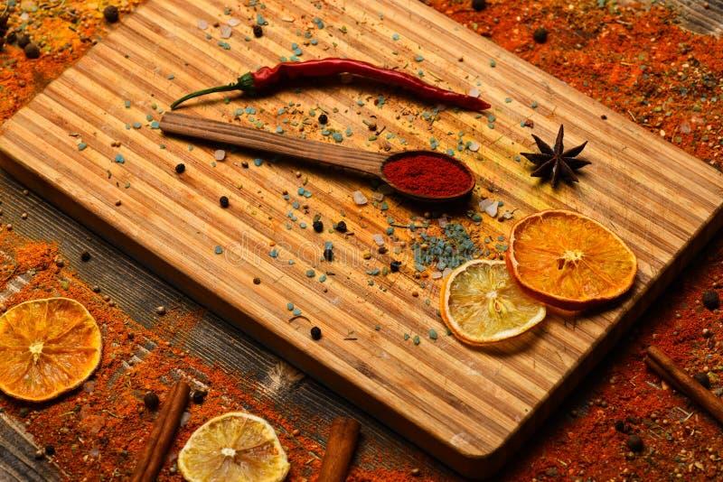 Begrepp för kulinariska konster Kryddor spridda runt om skärbräda Sked med kryddor på trätextur Sked som fylls med fotografering för bildbyråer