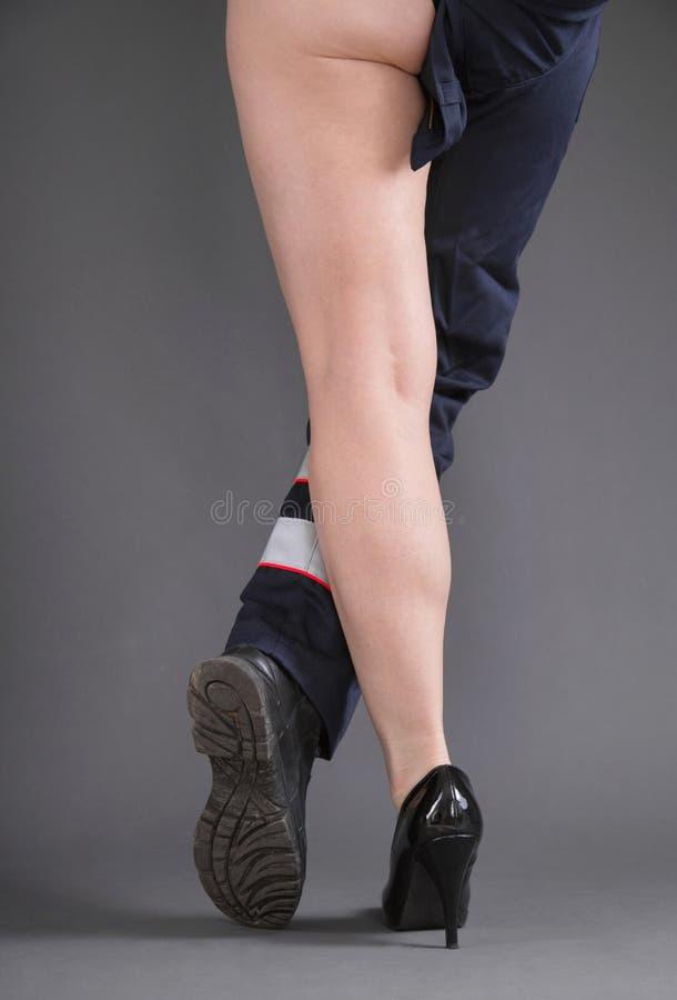 Begrepp för kvinnor i hantverket - ett sexigt kvinnaben och ett ben i M royaltyfria bilder