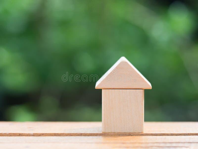 Begrepp för lånfastighethem Trähusminiatyr på trägolv med suddighetsgräsplanbakgrund royaltyfri bild