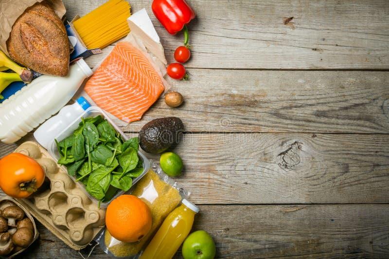 Begrepp för livsmedelsbutikshopping Allsidig kostbegrepp Nya foods med shoppingpåsen på lantlig wood bakgrund arkivbild